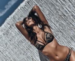 Enjoying summer heat.  Attractive young woman in bikini keeping hands behind head while posing outdoors