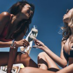 Toast to us! Two stunning young women in bikini enjoying champagne while sitting on the poolside outdoors