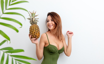 Portrait of young woman in swimsuit with pineapple and palm on white background. Summer season image concept