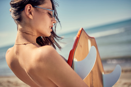 Beautiful sexy woman on the beach ready for surfing